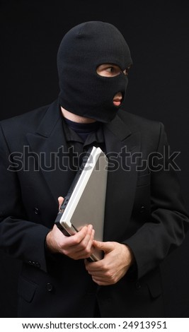 A business thief wearing a black balaclava is stealing a laptop computer