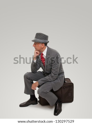A business traveler waiting seating on a suitcase - stock photo