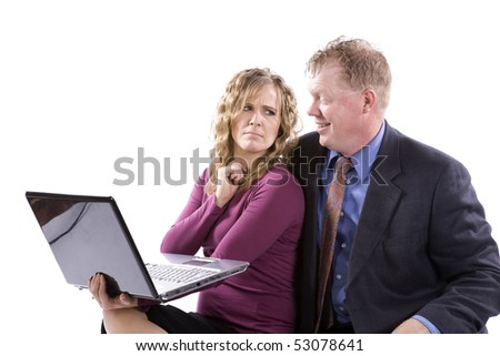 A business woman and man working together on a laptop he is happy about something and she is showing her frustration.