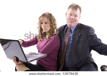 A business woman and man working together on a laptop she is pointing at something on the screen and the man is showing his confused expression.