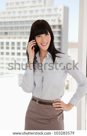 A business woman at work taking a call while smiling - stock photo