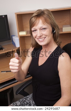 A business woman giving a thumbs up sign at her office desk - stock photo