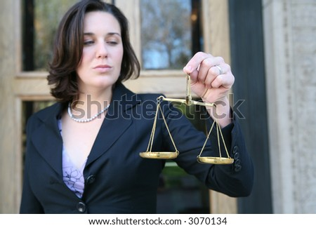 A business woman holding a justice scale outside the court building (Focus on hand with scale) - stock photo