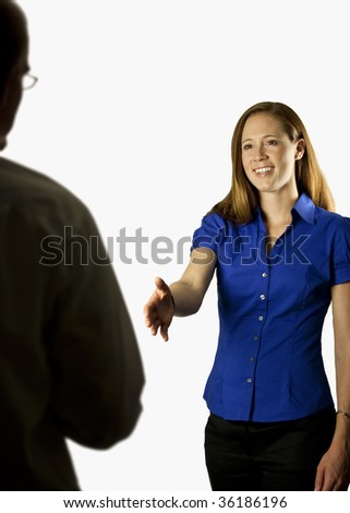 A business woman holding her hand out to shake with a business man - stock photo
