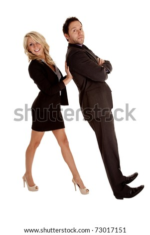 A business woman holding up her business man while he lays back on her hands. - stock photo