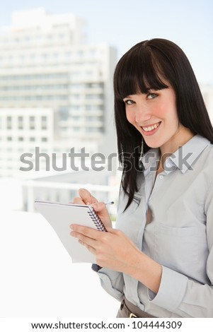 A business woman in her office looking at the camera as she writes on a notepad - stock photo