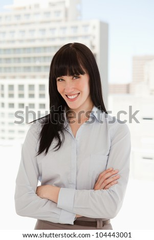 A business woman in her office smiling as she crosses her arms over - stock photo