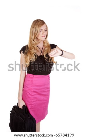 a business woman looking at her watch with a mad expression on her face while she is carring her bag.