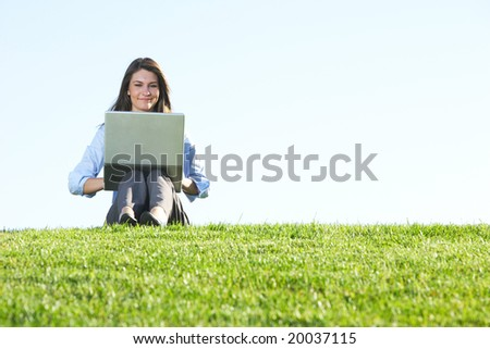 A business woman on a laptop in field out side the office