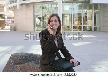 A business woman outside her workplace on the phone - stock photo