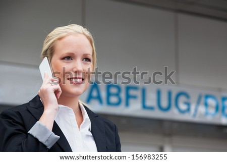 a business woman phoning with her cell phone at the airport. roaminggeb��?���¼rhen smartphones abroad - stock photo