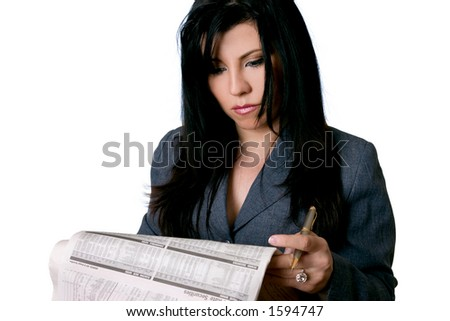 A business woman reading a newspaper with a serious expression or look of concentration. - stock photo