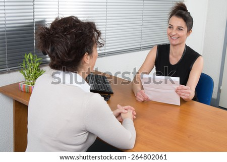A Business woman receives candidate for  a job at her office - stock photo