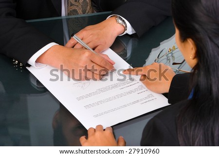 A business woman show the place on the document where the director should sign. - stock photo