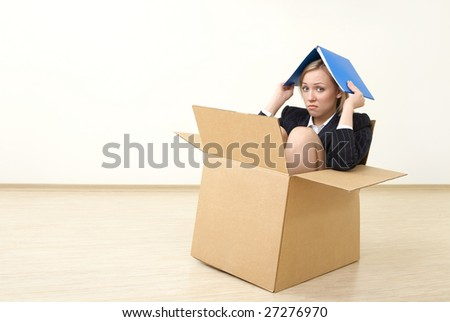 A business woman sits in a box, taking shelter a folder - stock photo