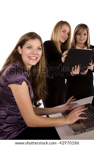 A business woman sitting at her desk , working on the computer with a smile on her face, with her co-workers happy too. - stock photo