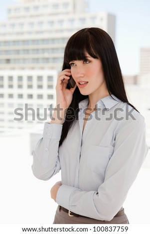 A business woman taking a call as she is at work - stock photo
