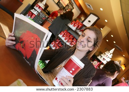 A business woman taking a coffee break and reading the newspaper - stock photo