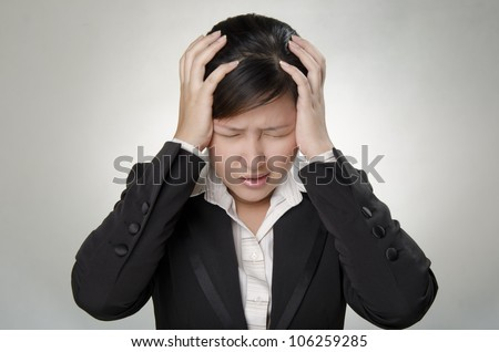 a business woman touching her head because of headache
