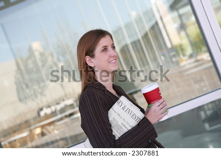 A business woman walking to work with coffee and the newspaper - stock photo