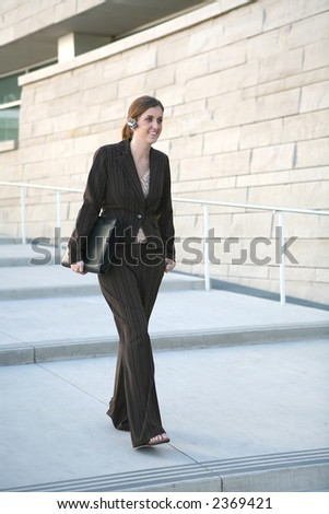 A business woman walking with briefcase and talking on the phone with earpiece - stock photo