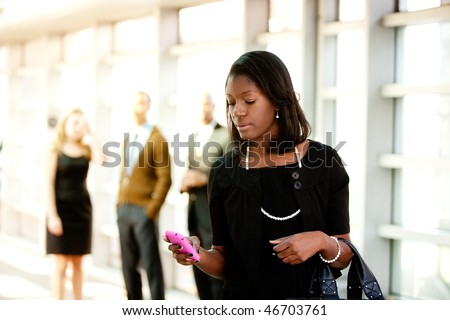 A business woman with a smart phone with colleagues in the background - stock photo