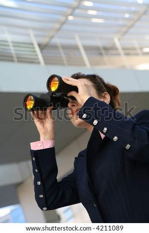 A business woman with binoculars outside her company - stock photo