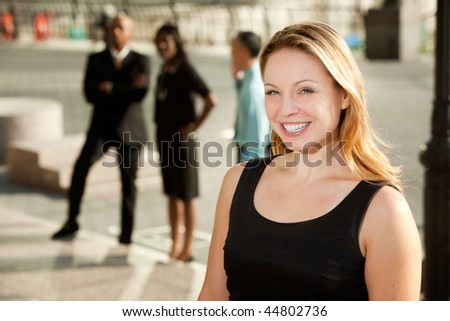 A business woman with colleagues in the background - stock photo