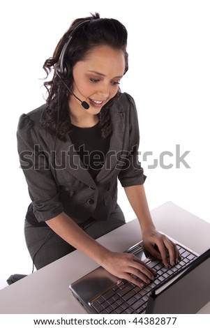A business woman working on her computer with her headset on.