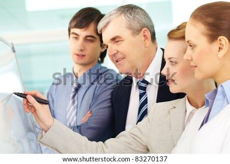 A business woman writing on whiteboard with a highlighter while explaining idea to colleagues - stock photo