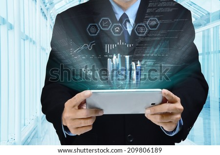 A businessman accessing internet and information technology via tablet / gadget in his hand - stock photo