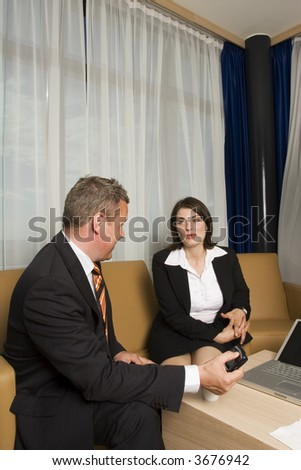 A businessman an businesswoman smartly dressed, having a meeting conversation in a  modern hotel suite