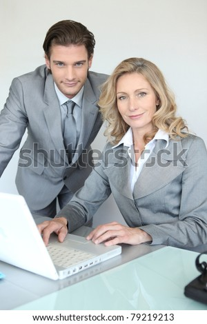 A businessman and a businesswoman working in front of a laptop and looking at us. - stock photo
