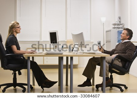 A businessman and woman are sitting across from each other at a desk in an office.  They are chatting with each other and looking away from the camera.  Horizontally framed shot.