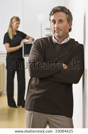A businessman and woman are standing in an office.  The woman is looking in a filing cabinet and the man is looking at the camera.  Vertically framed shot.