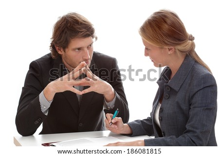 A businessman and woman exchanging mysterious glances at work - stock photo