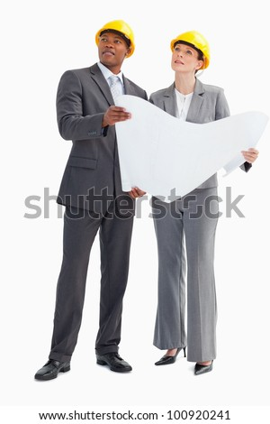 A businessman and woman wearing hard hats and holding a paper are looking up - stock photo