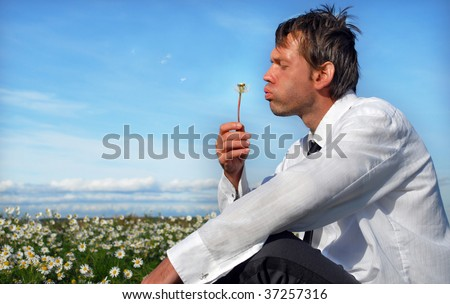 A businessman blowing dandelion on the meadow, he relxing after work - stock photo