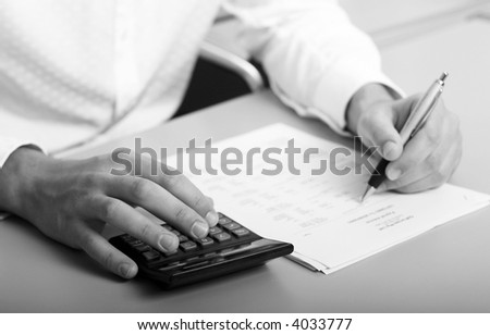 A businessman calculating expenses at tax time - stock photo