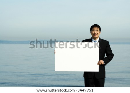 A businessman carrying a blank white board at the beach - stock photo