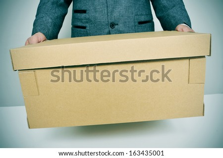 a businessman carrying a box, leaving or moving to a new office - stock photo