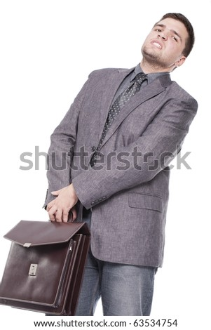 a businessman carrying a heavy briefcase - stock photo