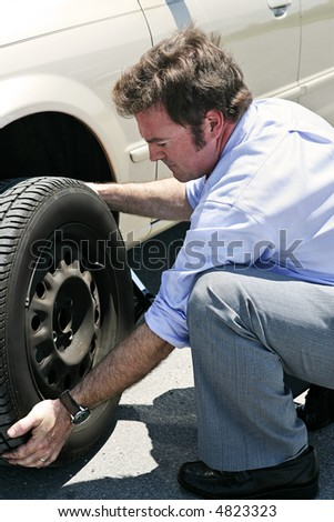 A businessman changing a flat tire on the road, red faced from the heat. - stock photo