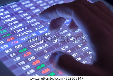 A businessman check stocks and market data on a touch screen device. Trading on stock market concept. Close up shot in the dark. - stock photo