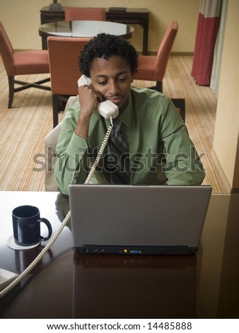 A businessman cheerfully reviews good results on his laptop computer in a hotel room during a business trip. - stock photo