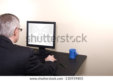 A businessman completing his basketball tournament bracket at work - stock photo