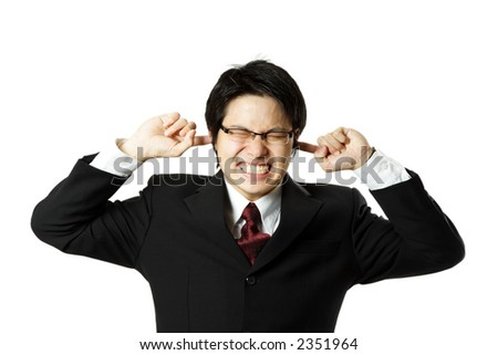 A businessman covering his ears with his fingers - stock photo