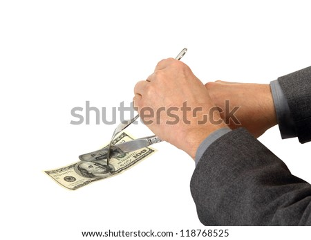 A businessman cuts costs with a fork and knife - stock photo