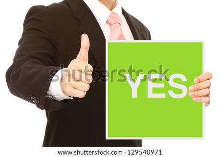 A businessman doing a thumbs up sign and holding signboard indicating Yes - stock photo