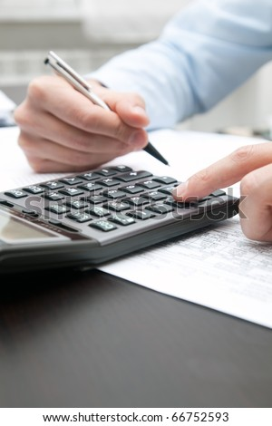 A businessman doing some paperwork using his calculator - stock photo
